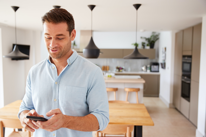 man managing smart thermostat from his mobile phone